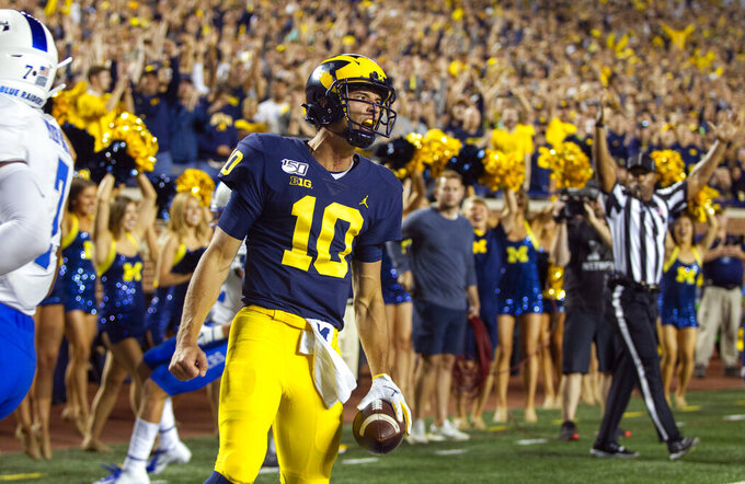 Michigan quarterback Dylan McCaffrey (10) celebrates his rushing touchdown during the third quarter of the team's NCAA football game against Middle Tennessee in Ann Arbor, Mich., Saturday, Aug. 31, 2019. Michigan won 40-21. (AP Photo/Tony Ding)