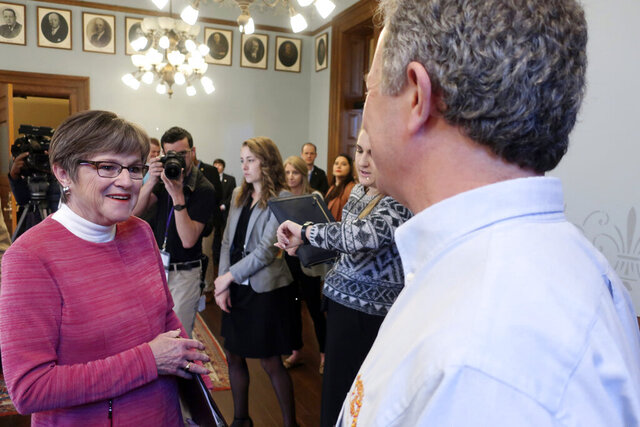 Kansas Gov. Laura Kelly, left, talks to Chuck Magerl, right, the owner of the Free State Brewing Company pub in Lawrence, Kan,, after a news conference to announce the launch of a new state loan program, Friday, March 20, 2020, at the Statehouse in Topeka, Kan. The new program will make $5 million in short-term, no-interest loans to bars, taverns, restaurants and motels struggling to cover their operating expenses. (AP Photo/John Hanna)