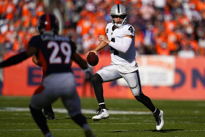 Las Vegas Raiders quarterback Derek Carr (4) runs as Denver Broncos cornerback Bryce Callahan (29) defends during the first half of an NFL football game, Sunday, Oct. 17, 2021, in Denver. (AP Photo/Jack Dempsey)