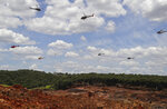 FILE - In this Feb. 1, 2019, file photo, helicopters hover over an iron ore mining complex to release thousands of flower petals paying homage to the dozens of victims killed and scores of missing after a mining dam collapsed there a week earlier, in Brumadinho, Brazil. The Danish pension fund for academics began selling off its stake in a Brazilian mining company, Vale, after two of the company's tailings dams collapsed, killing hundreds of people. So did Sweden's national pension. The main goal of institutional investors is to maximize returns. But now, more than ever, many are considering issues such as climate change and human rights. (AP Photo/Andre Penner, File)