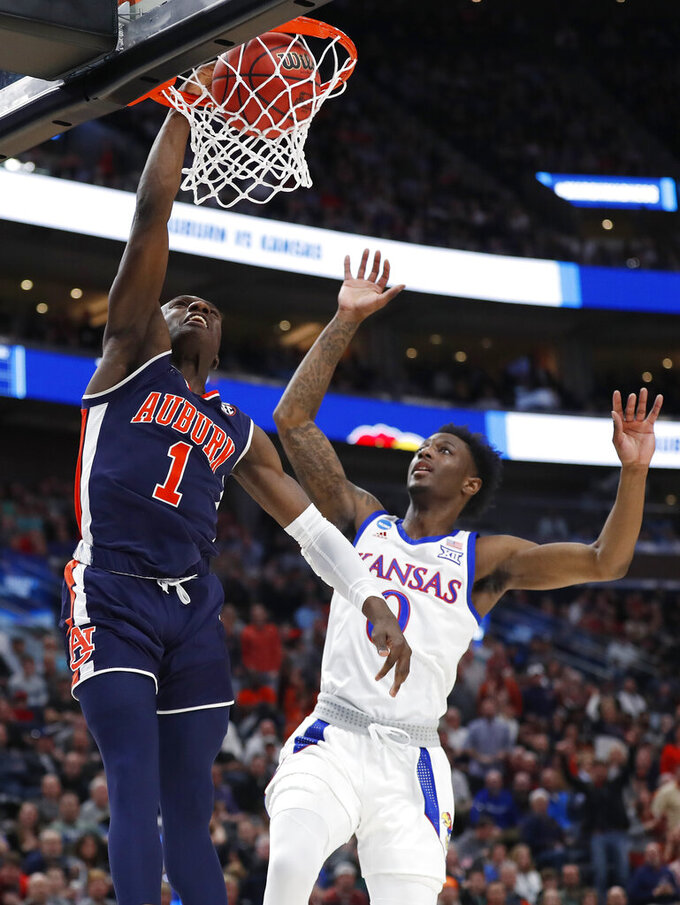 Auburn guard Jared Harper (1) dunks the ball against Kansas guard Marcus Garrett (0) during the first half of a second-round game in the NCAA men's college basketball tournament Saturday, March 23, 2019, in Salt Lake City. (AP Photo/Jeff Swinger)