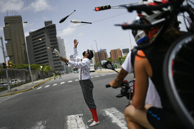 A street juggler wearing a protective face mask, performs at a street crossing during a red light in Caracas, Venezuela, Saturday, July 11, 2020, amid a government-ordered lockdown to curb the spread of the new coronavirus.(AP Photo/Matias Delacroix)