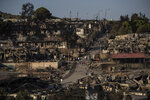Refugees and migrants walk inside the destroyed Moria camp on Lesbos island, Greece, Wednesday, Sept. 9, 2020. More than 12,000 people were left homeless after fires gutted the sprawling Moria refugee camp. The camp's life ended as it began, in drama: Successive fires that started before dawn on Sept. 9 devastating the site and making 12,000 inhabitants homeless during a COVD-19 lockdown. (AP Photo/Petros Giannakouris)