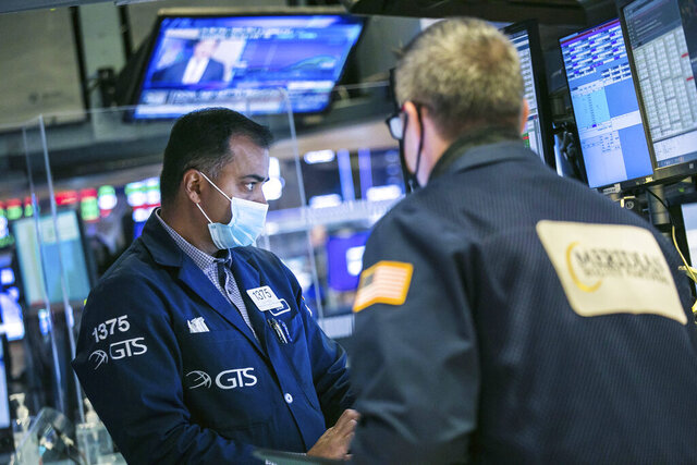 In this photo, provided by the New York Stock Exchange, specialist Dilip Patel, left, works with a trader on the floor of the NYSE, Thursday, Nov. 19, 2020. U.S. stocks are drifting in mixed trading on Thursday, as Wall Street's tug of war continues between worries about the worsening pandemic in the present and optimism that a vaccine will come in the future. (Courtney Crow/New York Stock Exchange via AP)