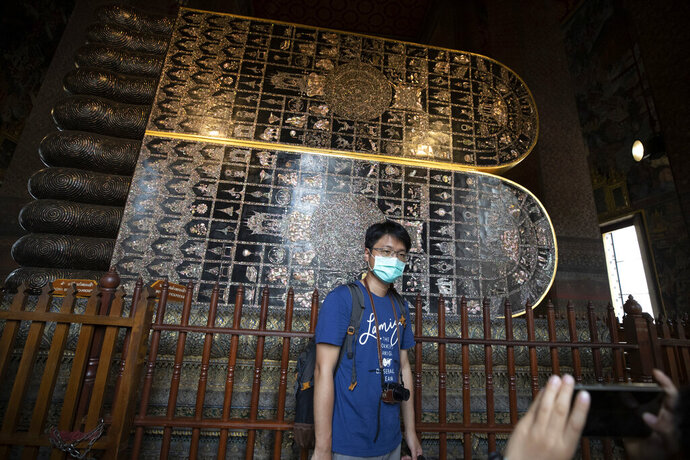 In this Feb. 7, 2020, photo, a masked tourist poses for a souvenir photo at Wat Pho in Bangkok, Thailand. There were less crowds in Bangkok's popular Wat Pho, a centuries-old Buddhist temple known for its giant reclining buddha, due to the virus scare. The complex of temples is normally visited by thousands of tourists. (AP Photo/Sakchai Lalit)