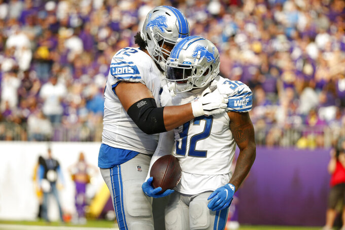Detroit Lions running back D'Andre Swift (32) celebrates with teammate guard Halapoulivaati Vaitai (72) after scoring on a 7-yard touchdown run during the second half of an NFL football game against the Minnesota Vikings, Sunday, Oct. 10, 2021, in Minneapolis. (AP Photo/Bruce Kluckhohn)