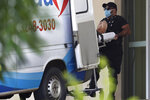 A patient suspected of having COVID-19 is transferred from an ambulance to the Regional Hospital of Samambaia, which specializes in the care of new coronavirus cases in Brasilia, Brazil, Thursday, Jan. 7, 2021. (AP Photo/Eraldo Peres)