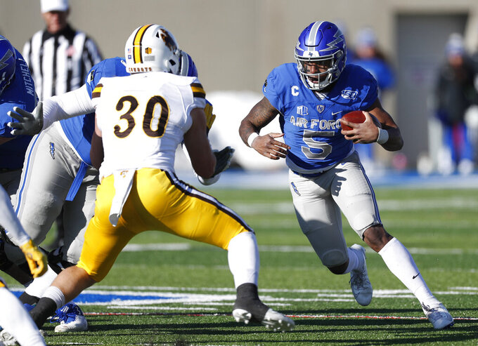 Wyoming linebacker Logan Wilson, left, comes in to tackle Air Force quarterback Donald Hammond III after a short gain in the second half of an NCAA college football game Saturday, Nov. 30, 2019, at Air Force Academy, Colo. Air Force won 20-6. (AP Photo/David Zalubowski)
