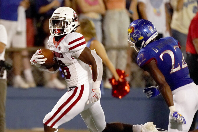 South Dakota running back Shomari Lawrence, left, gets past Kansas cornerback Duece Mayberry (22) to score a touchdown during the second half of an NCAA college football game Friday, Sept. 3, 2021, in Lawrence, Kan. Kansas won 17-14. (AP Photo/Charlie Riedel)