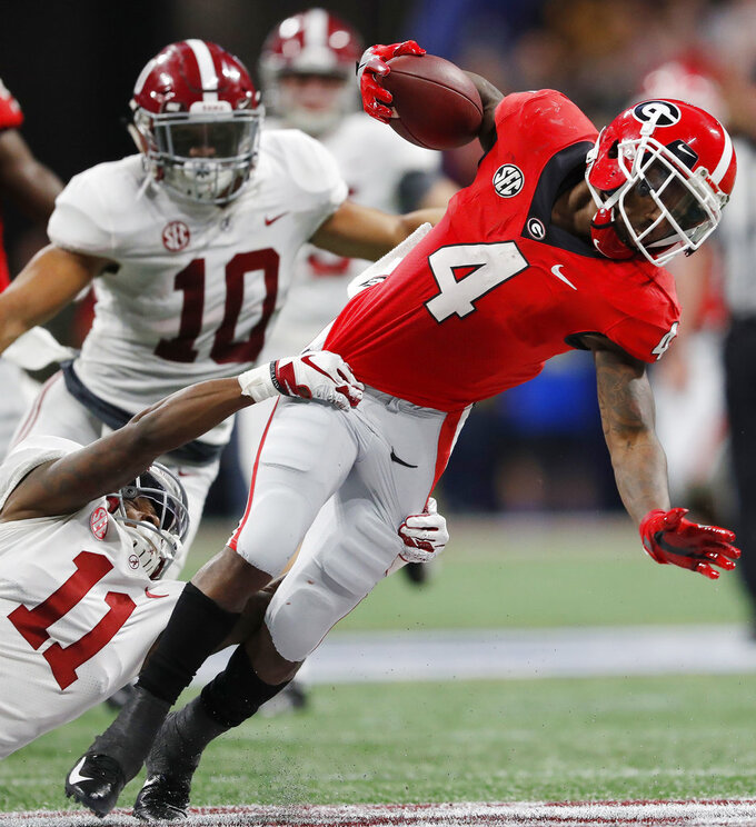 Alabama's Henry Ruggs III (11) tackles Georgia wide receiver Mecole Hardman (4) on a punt return during the second half of the Southeastern Conference championship NCAA college football game, Saturday, Dec. 1, 2018, in Atlanta. (AP Photo/John Bazemore)
