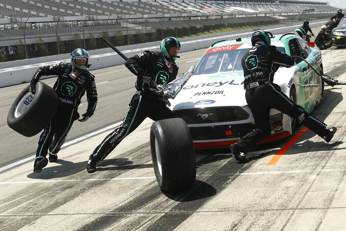 Crew members hustle to service the car of Austin Cindric in a pit stop during the NASCAR Xfinity Series auto race at Pocono Raceway, Sunday, June 28, 2020, in Long Pond, Pa. (AP Photo/Matt Slocum)