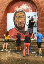 Community members work to clean up the George Floyd mural painted in the summer of 2020 at 6th and Ferry Streets, after white paint was thrown at the mural and it had to be removed by a fire hose, Monday, Aug. 30, 2021, in Lafayette, Ind. Lafayette police said two white males were seen throwing a bucket of white paint about 6 p.m. Monday at the mural in the city's downtown. (Nikos Frazier/Journal & Courier via AP)