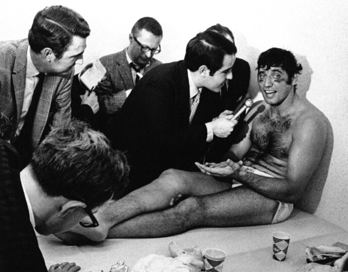 FILE - In this Jan. 13, 1969, file photo, New York Jets quarterback Joe Namath talks with reporters as he rests on a training table in the teams dressing room the morning after the Jets defeated the Baltimore Colts 16-7 in Super Bowl III in Miami, Fla. Namath is the NFL's greatest character. Guaranteed.  The Pro Football Hall of Fame quarterback who guaranteed his three-touchdown underdog New York Jets would beat the mighty Baltimore Colts in the third Super Bowl was a solid choice in balloting conducted by The Associated Press in conjunction with the league's celebration of its 100th season. (AP Photo/File)