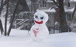 A snowman stands in a yard in Lake Zurich, Ill., during a winter storm, Tuesday, Jan. 26. 2021. (Paul Valade/Daily Herald via AP)
