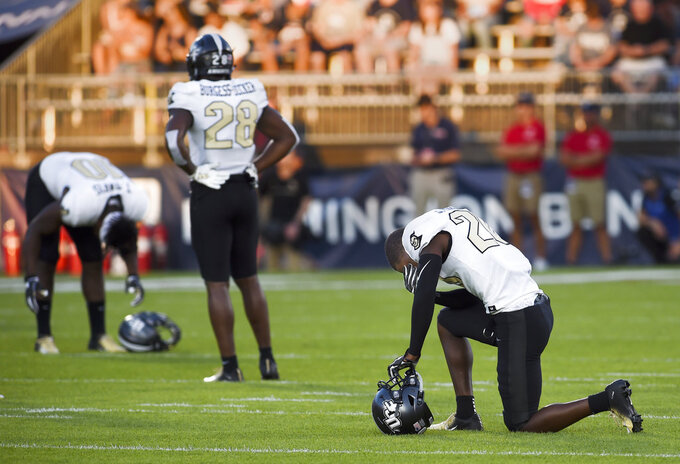 Central Florida players wait after an injury that occurred during the opening play of the game of an NCAA college football game Thursday, Aug. 30, 2018, in East Hartford, Conn. UCF defensive back Aaron Robinson was injured on the opening kickoff in the game against Connecticut. (AP Photo/Stephen Dunn)