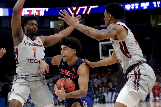 Liberty guard Elijah Cuffee, middle, drives to the basket between Virginia Tech guard Isaiah Wilkins, left, and guard Nickeil Alexander-Walker during the first half of a second-round game in the NCAA men's college basketball tournament Sunday, March 24, 2019, in San Jose, Calif. (AP Photo/Jeff Chiu)