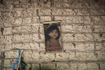 In this Sept. 2, 2019 photo, the image of a child hangs on an adobe wall inside her home in the Ka 'a kyr village, Para state, Brazil. Brazil's President Jair Bolsonaro believes past allocations of land to indigenous people were excessive. About 14% of Brazil is indigenous territory, a huge area for a relatively small population, according to Bolsonaro. (AP Photo/Rodrigo Abd)