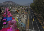 Pink tarps protect street stalls from the sun, as a reduced, but still active, street market takes place alongside a virtually deserted highway, in Mexico City, Sunday, March 29, 2020. In a little more than a week, Mexico has gone from seeing its president giving kisses and hugs at his events to the first firm call from the government for the populace to stay at home, due to the coronavirus. (AP Photo/Rebecca Blackwell)