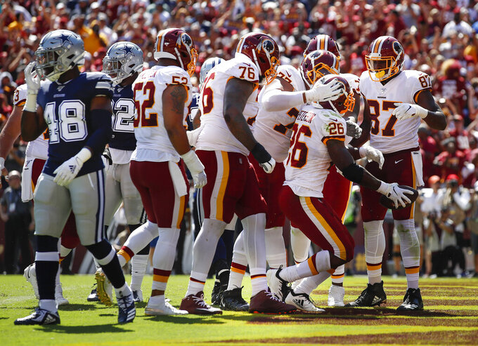 Washington Redskins running back Adrian Peterson (26) begins to celebrate his touchdown against the Dallas Cowboys with his teammates in the first half of an NFL football game, Sunday, Sept. 15, 2019, in Landover, Md. (AP Photo/Alex Brandon)