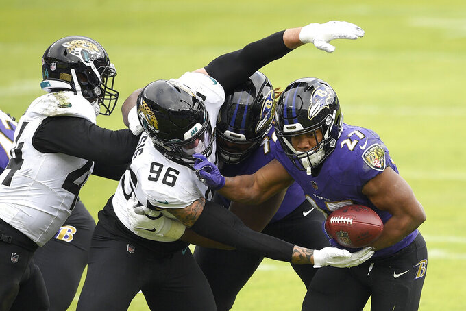 Jacksonville Jaguars defensive end Adam Gotsis (96) knocks the ball out of the hands of Baltimore Ravens running back J.K. Dobbins (27) during the first half of an NFL football game, Sunday, Dec. 20, 2020, in Baltimore. The Ravens recovered the fumble. (AP Photo/Nick Wass)