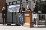 In this photo provided by Purdue University, Sean English, right, the inaugural recipient of the Tyler Trent Courage and Resilience Award, speaks as Tyler's parents Kelly, left, and Tony Trent, and Purdue President Mitch Daniels look on during a news conference at the entrance of Ross-Ade Stadium, Wednesday, March 27, 2019, in West Lafayette, Ind. A rendering of the memorial gate honoring Tyler Trent at the entrance of Ross-Ade Stadium is displayed between the couple. (Rebecca Wilcox/Purdue University via AP)