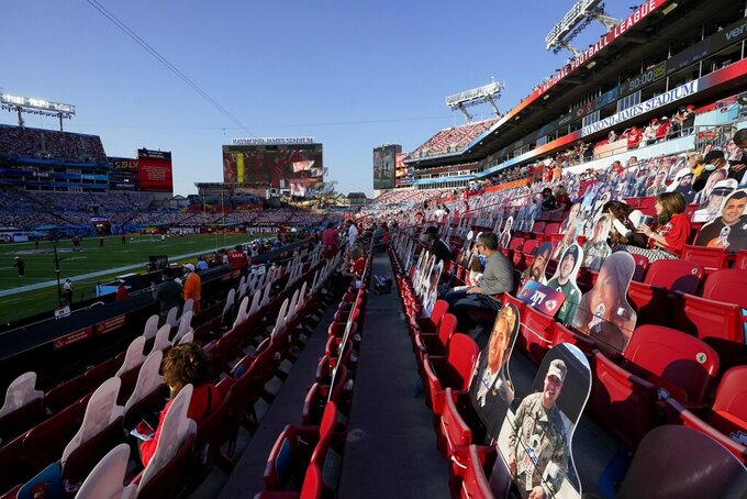 Fans sit near cutouts in the stands at Raymond James Stadium before the NFL Super Bowl 55 football game between the Kansas City Chiefs and Tampa Bay Buccaneers, Sunday, Feb. 7, 2021, in Tampa, Fla. (AP Photo/Gregory Bull)