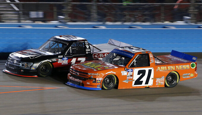Zane Smith (21) races past Dylan Lupton (17) during the NASCAR Truck Series auto race at Phoenix Raceway, Friday, Nov. 6, 2020, in Avondale, Ariz. (AP Photo/Ralph Freso)