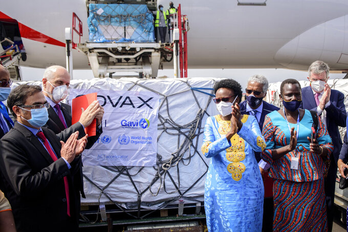 Uganda's Minister of Health Dr. Jane Ruth Aceng, center right, and other officials greet the country's first consignment of AstraZeneca COVID-19 vaccine manufactured by the Serum Institute of India and provided through the global COVAX initiative, at the airport in Entebbe, Uganda Friday, March 5, 2021. Urgent calls for COVID-19 vaccine fairness rang through African countries on Friday as more welcomed or rolled out doses from the global COVAX initiative, with officials acutely aware their continent needs much more. (AP Photo/Nicholas Bamulanzeki)