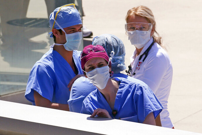 FILE - In this Thursday, April 30, 2020 file photo, Health care workers look on during a flyover at the University of Utah Hospital in Salt Lake City. One of Utah's largest hospitals had no beds left Friday, Oct. 16, 2020 in its regular intensive-care unit as the governor declared the state's weeks long spike in coronavirus cases