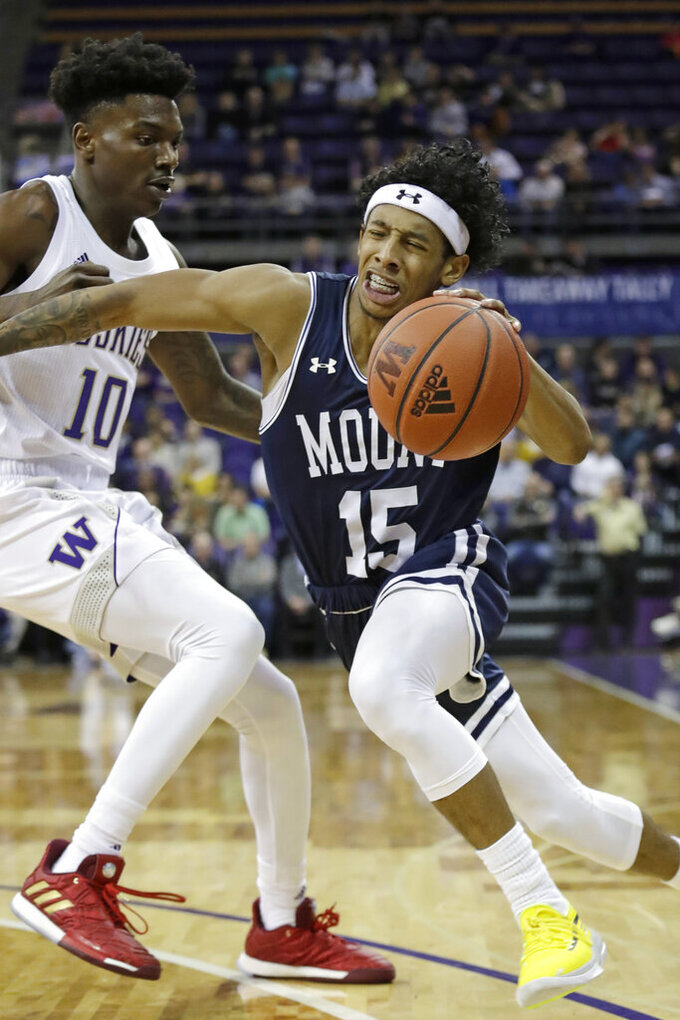 Mount St. Mary's's Damian Chong Qui (15) tries to drive past Washington's Elijah Hardy during the first half of an NCAA college basketball game Tuesday, Nov. 12, 2019, in Seattle. (AP Photo/Elaine Thompson)