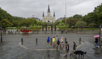 People walk past Jackson Square and St. Louis Cathedral in the French Quarter before landfall of Tropical Storm Barry from the Gulf of Mexico in New Orleans, La., Friday, July 12, 2019. (AP Photo/Matthew Hinton)