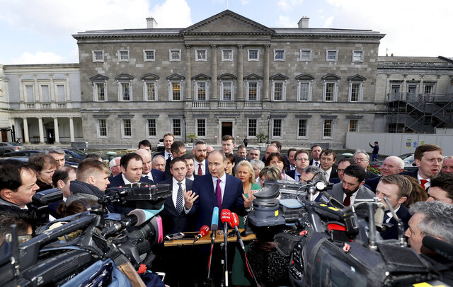 Fianna Fail leader Micheal Martin, center, with party lawmakers, speaks to the media on the plinth at Leinster House, Dublin, Thursday, Feb. 20, 2020. Ireland's parliament convened Thursday for the first time since an election two weeks ago that left three parties on roughly level pegging, with no easy route to forming a stable government. Talks among the parties have failed to make much progress since the Feb. 8 election, which brought a breakthrough for left-wing nationalists Sinn Fein at the expense of the two long-dominant centrist parties, Fianna Fail and Fine Gael. (Brian Lawless/PA via AP)