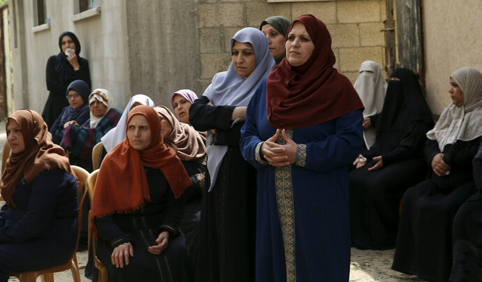 Relatives mourn while waiting for the body of Jihad Hararah, in front of his family house during his funeral in Shijaiyah neighborhood in Gaza City, Saturday, March 23, 2019. Gaza's Health Ministry said Hararah, died shortly after he shot at his face yesterday by Israeli troops during a protest at the Gaza Strip's border with Israel. (AP Photo/Adel Hana)