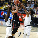 Utah forward Timmy Allen, center, shoots between Colorado guards McKinley Wright IV, left, and D'Shawn Schwartz during the first half of an NCAA college basketball game Saturday, March 2, 2019, in Boulder, Colo. (AP Photo/David Zalubowski)