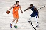 Phoenix Suns' Dario Saric (20) brings the ball down the court as Dallas Mavericks' Michael Kidd-Gilchrist (9) defends during the second half of an NBA basketball game Thursday, Aug. 13, 2020 in Lake Buena Vista, Fla. (AP Photo/Ashley Landis, Pool)