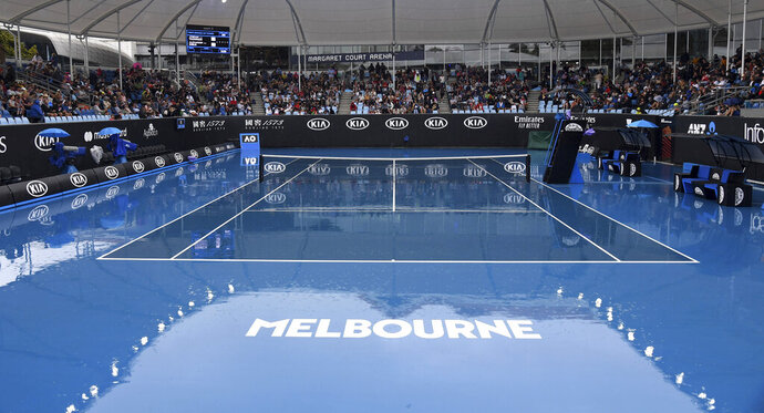 Spectators wait as rain stops plays during a first round singles match at the Australian Open tennis championship in Melbourne, Australia, Monday, Jan. 20, 2020. (AP Photo/Andy Brownbill)