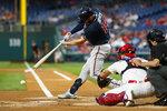 Atlanta Braves' Matt Joyce, left, hits into a run-scoring double play during the first inning of a baseball game against the Philadelphia Phillies, Monday, Sept. 9, 2019, in Philadelphia. (AP Photo/Matt Slocum)