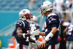 New England Patriots quarterback Tom Brady (12) greets wide receiver Antonio Brown (17) before the start of an NFL football game against the Miami Dolphins, Sunday, Sept. 15, 2019, in Miami Gardens, Fla. (AP Photo/Brynn Anderson)