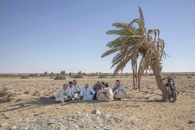 55-year-old Egyptian farmer Makhluf Abu Kassem, center, sits with farmers under shade of a dried up palm tree surrounded by barren wasteland that was once fertile and green, in Second Village, Qouta town, Fayoum, Egypt, Wednesday, Aug. 5, 2020. Abu Kassem fears that a dam Ethiopia is building on the Blue Nile, the Nile's main tributary, could add to the severe water shortages already hitting his village if no deal is struck to ensure a continued flow of water.