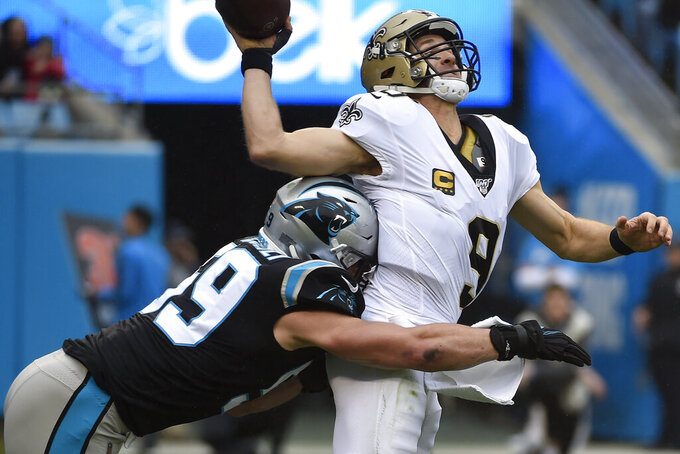 Carolina Panthers middle linebacker Luke Kuechly (59) hits New Orleans Saints quarterback Drew Brees (9) during the first half of an NFL football game in Charlotte, N.C., Sunday, Dec. 29, 2019. (AP Photo/Mike McCarn)