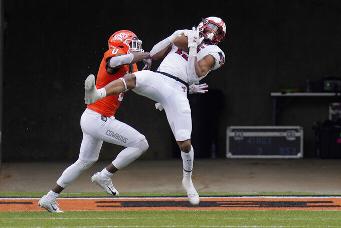 Texas Tech wide receiver Erik Ezukanma (13) catches a pass for a touchdown in front of Oklahoma State cornerback Christian Holmes (0) in the second half of an NCAA college football game in Stillwater, Okla., Saturday, Nov. 28, 2020. (AP Photo/Sue Ogrocki)