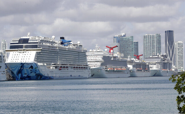 Cruise ships are docked at PortMiami, Tuesday, March 31, 2020, in Miami. The U.S. Coast Guard said Tuesday that it's working with Holland America on a detailed docking plan that would require two ships carrying passengers and crew from an ill-fated cruise to handle all medical issues without impacting South Florida's already-stressed hospitals.  (AP Photo/Wilfredo Lee)