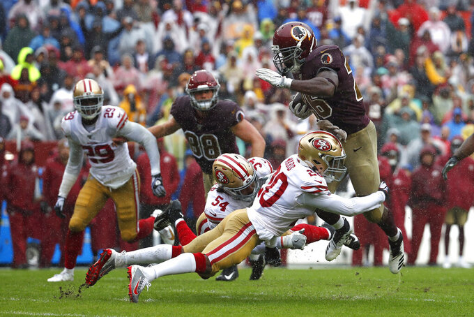 Washington Redskins running back Adrian Peterson, right, rushes against San Francisco 49ers cornerback Jimmie Ward (20) in the first half of an NFL football game, Sunday, Oct. 20, 2019, in Landover, Md. (AP Photo/Alex Brandon)