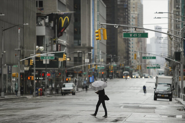 A pedestrians crosses a mostly empty Sixth Avenue during the coronavirus outbreak, Friday, April 3, 2020, in New York. The new coronavirus causes mild or moderate symptoms for most people, but for some, especially older adults and people with existing health problems, it can cause more severe illness or death. (AP Photo/Frank Franklin II)