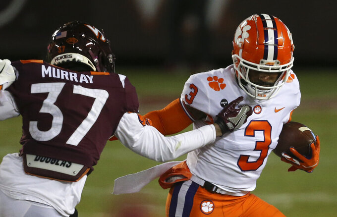 Clemson's Amari Rodgers, right, tries to escape from Virginia Tech's Brion Murray 37 during the first quarter of an NCAA college football game Saturday, Dec. 5, 2020, in Blacksburg, Va. (Matt Gentry/The Roanoke Times via AP, Pool)
