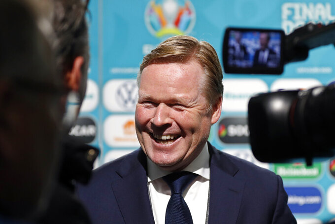 FILE- In this Nov. 30, 2019 file photo, soccer coach Ronald Koeman smiles while talking to journalists after the draw for the UEFA Euro 2020 soccer tournament finals in Bucharest, Romania. Barcelona officially announced on Wednesday Aug. 19, 2020a deal with Koeman to become their coach five days after the team's humiliating 8-2 loss to Bayern Munich in the Champions League quarterfinals. Barcelona says the former defender's deal runs through June 2022. Koeman replaces the fired Quique Setien.(AP Photo/Petr David Josek, File)