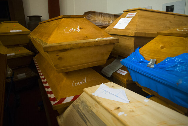 Caskets labelled with the word 'Covid' are stacked with others coffins in the memorial hall of the crematorium in Meissen, Germany, Monday, Jan. 11, 2021. The crematorium would typically have 70 to 100 caskets on site at this time of year, now it has 300 bodies waiting to be cremated and more are brought to the crematorium every day. (AP Photo/Markus Schreiber)