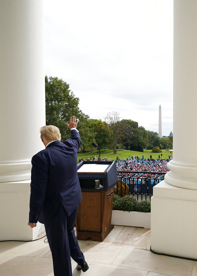 FILE - In this Oct. 10, 2020, file photo President Donald Trump waves from the Blue Room Balcony of the White House to a crowd of supporters in Washington. The most improbable of presidents, Donald Trump reshaped the office and shattered its centuries-old norms and traditions while dominating the national discourse like no one before. (AP Photo/Alex Brandon, File)