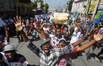 Protesters demand the resignation of Haitian President Jovenel Moise during a march led by the art community in Port-au-Prince, Haiti, Sunday, Oct. 13, 2019. Protests have paralyzed the country for nearly a month, shuttering businesses and schools. (AP Photo/Rebecca Blackwell)