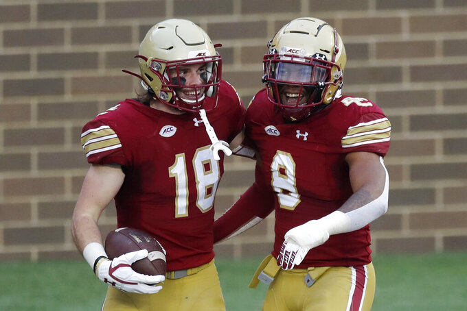Boston College defensive back Mike Palmer (18) celebrates his touchdown with defensive back Jahmin Muse (8) after a turnover during the first half of an NCAA college football game against Georgia Tech, Saturday, Oct. 24, 2020, in Boston. (AP Photo/Michael Dwyer)